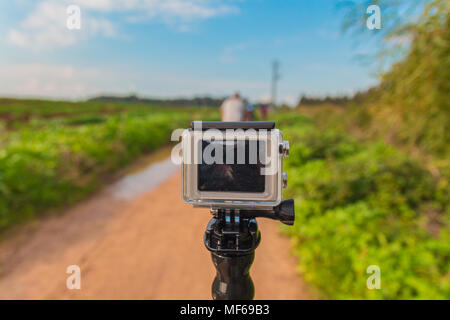 GoPro action camera on stick in dirt road at rural area. - Stock Photo