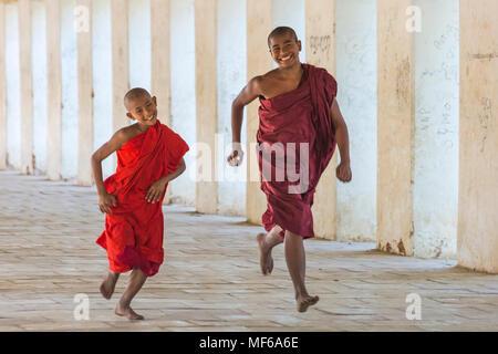 Novice Buddhist monks enjoying themselves running along eastern stair way of Shwezigon Pagoda, Nyaung U, Bagan, Myanmar (Burma), Asia in February - Stock Photo