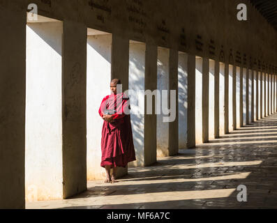 Novice Buddhist monk standing in eastern stair way of Shwezigon Pagoda, Nyaung U, Bagan, Myanmar (Burma), Asia in February - columns and shadows - Stock Photo