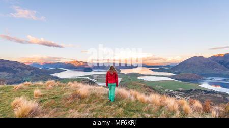 Hiker overlooking Lake Wanaka and mountains, sunset, Rocky Peak, Glendhu Bay, Otago, Southland, New Zealand - Stock Photo