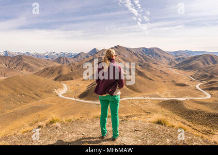 Woman looking over stark mountains, Lindis Pass, Southern Alps, Otago, Southland, New Zealand - Stock Photo