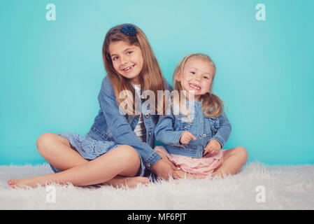 smiling sisters sitting on the floor on blue background - Stock Photo