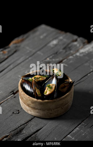 closeup of a boxwood bowl with moules mariniere, a french recipe of mussels, on a rustic wooden table - Stock Photo