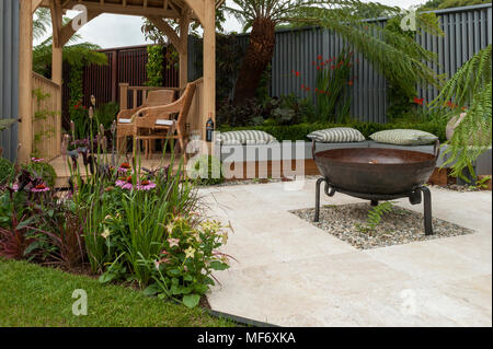 Seating areas, gazebo, patio fire pit & flowers in tropical style show garden - Visit Plantation: Colonial Chic and Bajan Roots. RHS Show Tatton Park. - Stock Photo