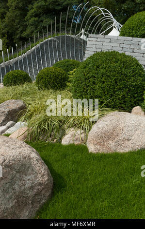 Dramatic metal sculpture, white stones, grasses & buxus represent waves & shoreline - 'Wave Dance' garden, RHS Flower Show, Tatton Park, England, UK. - Stock Photo