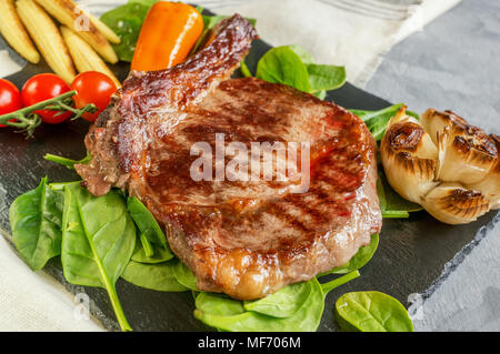 Rare steak with blood pepper garlic tomatoes broccoli grilled on a slate plate. - Stock Photo