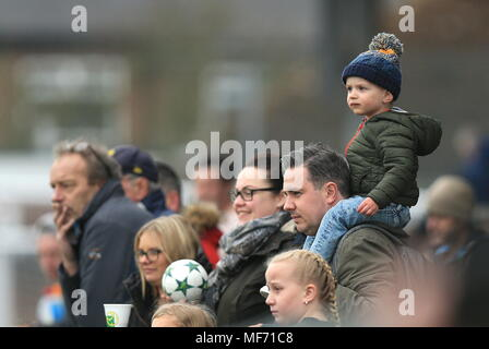 Watching, Dreaming, waiting and wondering when its going to be his turn to play. A child sits on his fathers shoulders during a county cup final. - Stock Photo