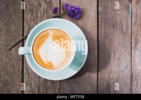 Top view of hot coffee in green cup with latte art on wooden plank table with forget me not flower,Food and drink concept,vintage filter - Stock Photo