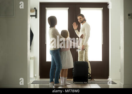 Smiling father waving goodbye to wife and daughter leaving home - Stock Photo