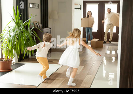 Rear view at kids running to parents on moving day - Stock Photo