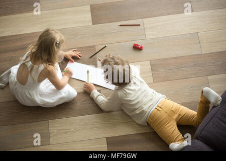 Kids playing drawing together on floor at home, top view - Stock Photo