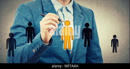 Businessman drawing small people icons, one of them is different colored, yellow among black. Employee choosing, group leadership concept. Select the  - Stock Photo