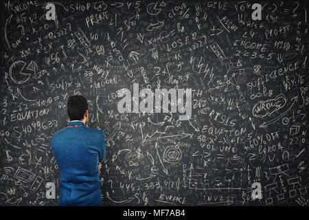 Rear view of a puzzled businessman in front of a huge blackboard try to solve hard mathematics calculation, formula and equations. Thinking of project - Stock Photo