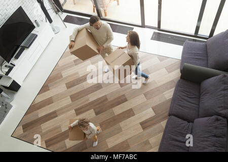Parents and son carrying boxes entering new home, top view - Stock Photo