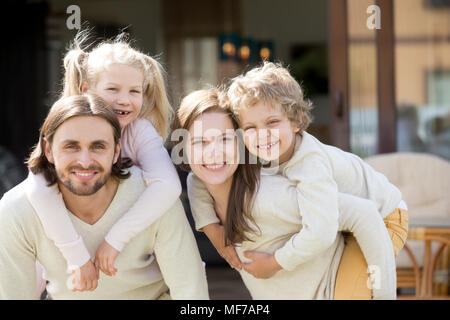 Happy parents piggybacking kids on house terrace looking at came - Stock Photo