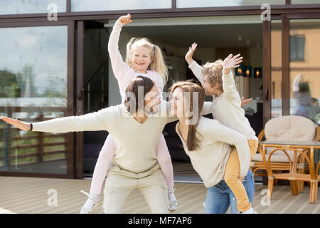 Smiling parents piggybacking playing with kids spending time out - Stock Photo