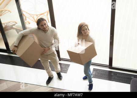 Young couple holding moving boxes entering new house, overhead v - Stock Photo