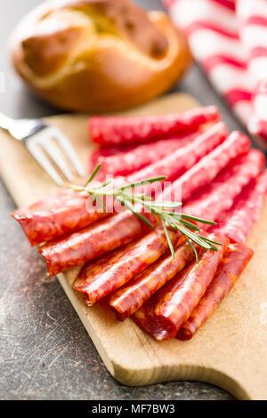 Slices of chorizo salami sausage on cutting board. - Stock Photo