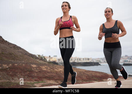 Two pretty women running along the boardwalk in modern tights and crop tops with hair tied back - Stock Photo