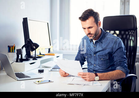 Man reading document at desk in office - Stock Photo