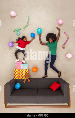 Little daughter celebrating birthday party, dancing with her mother - Stock Photo