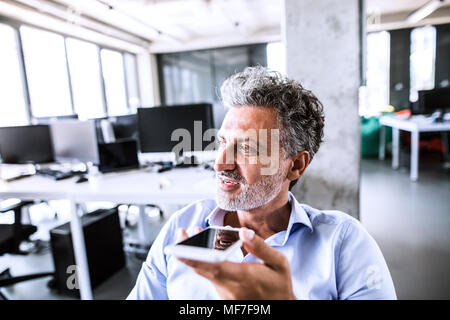 Portrait of mature businessman using smartphone in office - Stock Photo