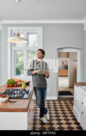 Man using tablet in kitchen looking at ceiling lamp - Stock Photo
