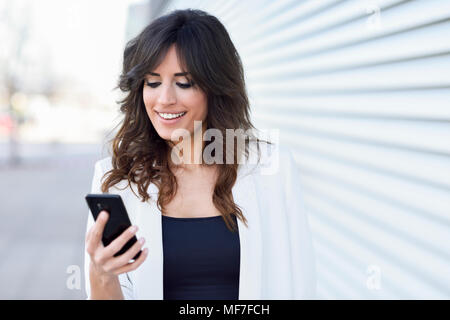 Portrait of smiling businesswoman looking at cell phone - Stock Photo