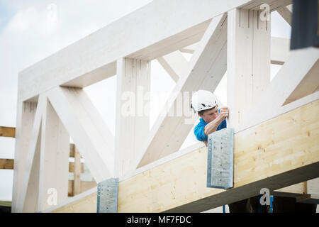 Austria, worker fixing roof construction - Stock Photo