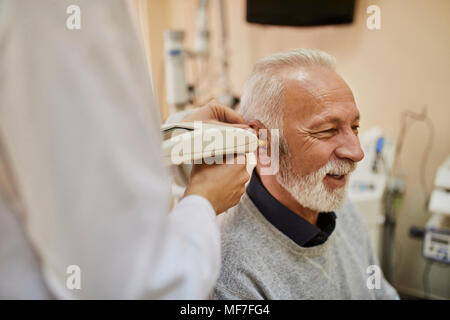 ENT physician examining ear of a senior man - Stock Photo