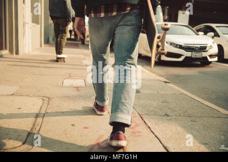 Low section of man walking on sidewalk with skateboard - Stock Photo
