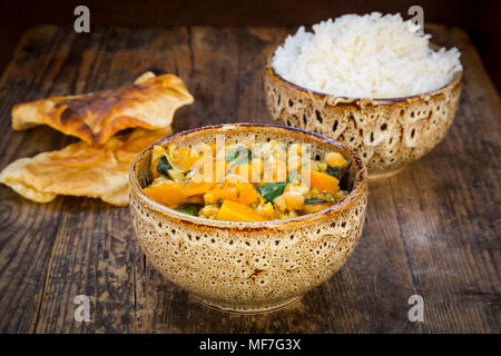 Curry dish with cauliflower, butternut pumpkin, spinach and coriander, papadam and rice - Stock Photo