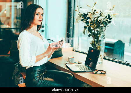 Pensive young businesswoman using smartphone in a coffee shop - Stock Photo