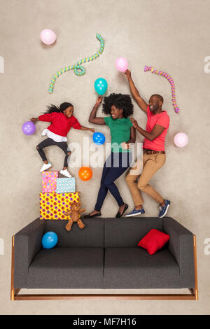 Little daughter celebrating birthday party, dancing with her parents - Stock Photo