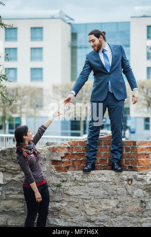 Businessman standing on a wall reaching out his hand for woman - Stock Photo