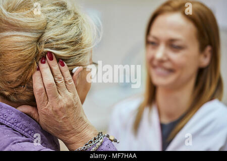 Female doctor and senior woman with hearing aid - Stock Photo