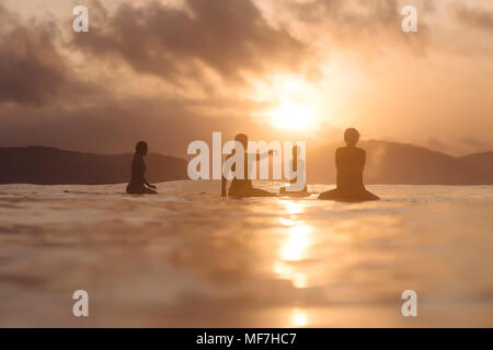 Indonesia, Lombok, group of surfers sitting on surfboards at sunset - Stock Photo