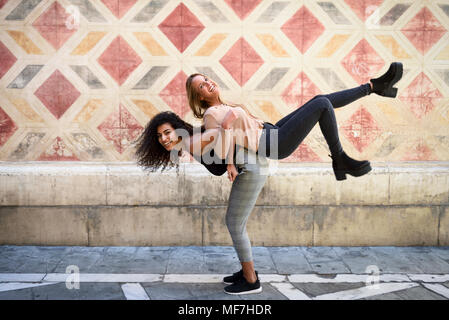 Laughing woman carrying her best friend piggyback - Stock Photo