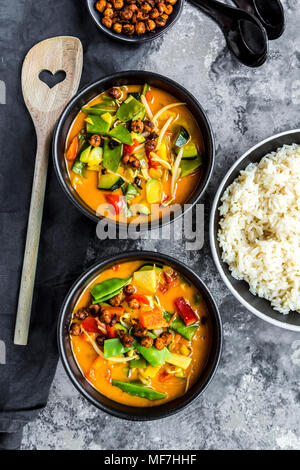Red curry in bowls, rice and roasted chickpeas - Stock Photo
