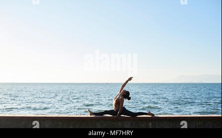 Young woman practicing yoga on a wall by the sea - Stock Photo