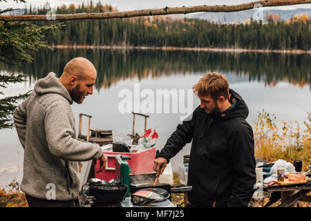Canada, British Columbia, two men cooking at Blue Lake - Stock Photo