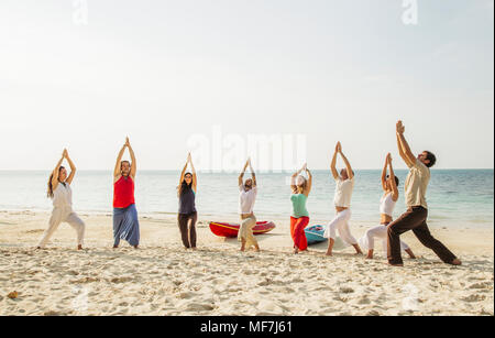 Thailand, Koh Phangan, group of people doing yoga on a beach - Stock Photo