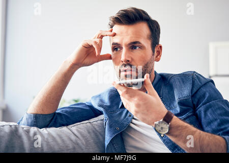 Worried man sitting on sofa using cell phone - Stock Photo