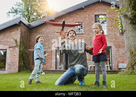 Father with two children playing with toy airplane in garden of their home - Stock Photo