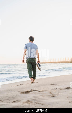 Back view of man walking barefoot on the beach - Stock Photo