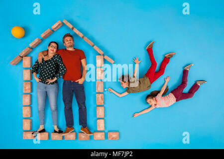 Parents standing in house, while children are coming home - Stock Photo