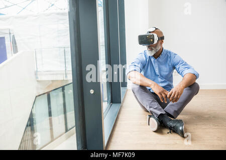 Businessman wearing VR glasses sitting on the floor at the window - Stock Photo