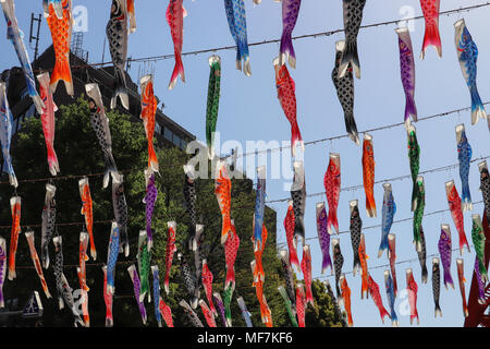 Many colorful paper fish lanterns or windsocks hang on diagonal strings high above the viewer against a blue sky; celebrate Children's Day in Japan. - Stock Photo