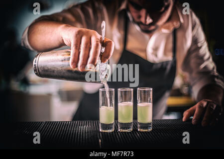 Bartender pouring fresh cocktail in short glass for service guest - Stock Photo