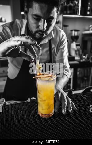 Bartender decorating non-alcoholic orange cocktail - Stock Photo